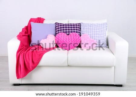 Pink heart shaped pillows, plaid on white sofa - stock photo