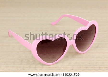Pink heart-shaped sunglasses on bamboo mat - stock photo