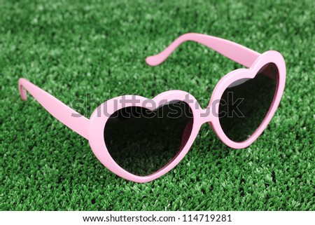 Pink heart-shaped sunglasses on green grass - stock photo