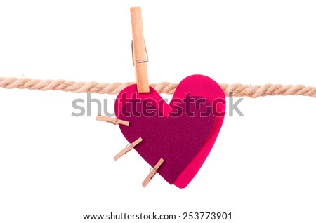 pink heart with small clothespins attached hanging on a rope clothesline isolated on white - stock photo