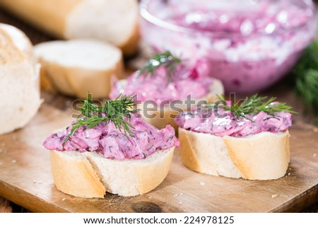 Pink Herring Salad (with beet and fresh herbs) on a piece of bread - stock photo