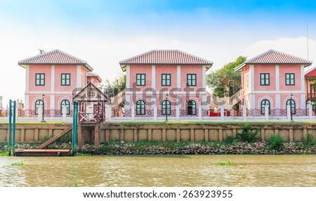 pink house in line beside the river in nature background - stock photo