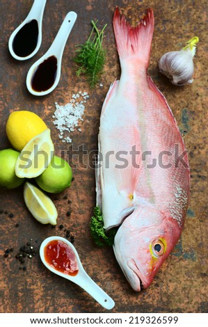 pink Hussar fish with cooking ingredients on copper rustic background - stock photo