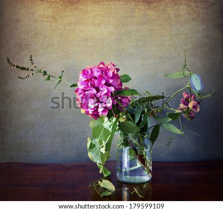 Pink hydrangea and field flowers in a glass with grunge texture and retro Instagram-like effects - stock photo