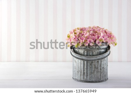 Pink hydrangea flowers in a metal bucket on vintage striped background with copy space - stock photo