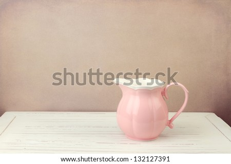 Pink jug on wooden vintage table - stock photo