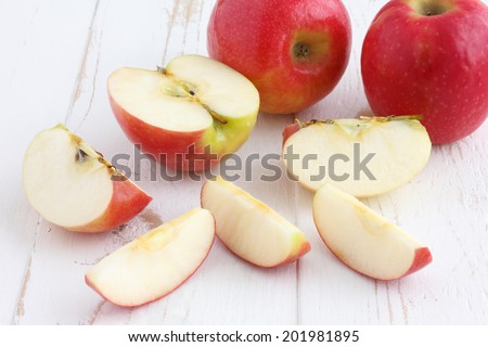 Pink lady apples cut on a painted white rustic wood table. - stock photo