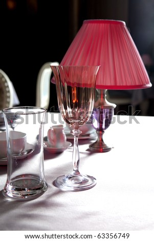 Pink lamp and pink glasses on the table in restaurant - stock photo