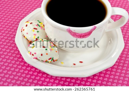 pink lipstick on coffee cup with cookies and sprinkles - stock photo