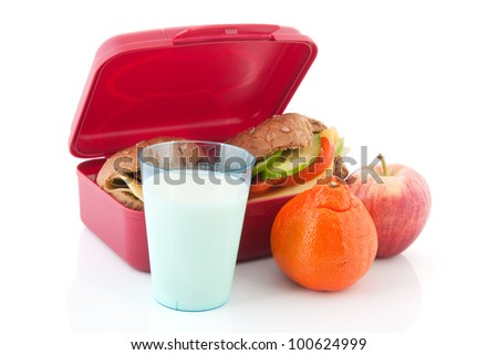 Pink lunchbox with healthy brown bread rolls cheese milk and vegetables - stock photo