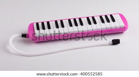 pink melodeon music instrument for child isolated on white - stock photo