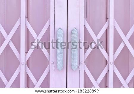 Pink metal grille sliding door with aluminium handle - stock photo
