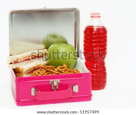 Pink metal lunchbox filled with peanut butter and jelly sandwich, pretzels and an apple with a drink to the side on an isolated white background - stock photo