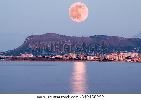 Pink Moon rising above sea and a small mountain. - stock photo