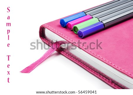 Pink notebook with colorful pens on a pure white background with space for text - stock photo