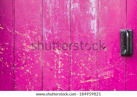 Pink old wooden door scarred with black handle ,background - stock photo