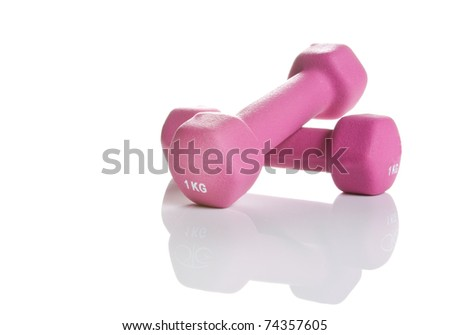 pink one kilogram weights isolated on white with reflection and copy space on right - stock photo