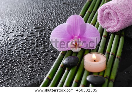 Pink orchid and bamboo grove,candle ,stones ,candle on wet black background   - stock photo