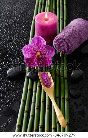 Pink orchid and bamboo grove, towel, spoon on wet black background   - stock photo