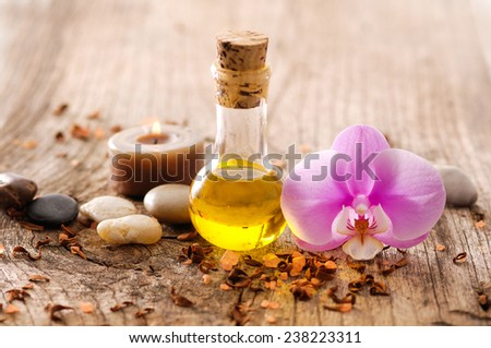 Pink orchid and stones ,massage oil ,candle on old wood - stock photo