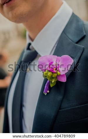 Pink orchid boutonniere on the grooms suit - stock photo