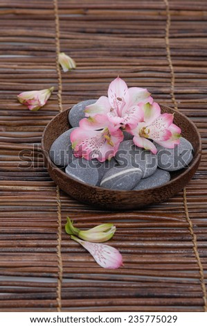 Pink orchid with gray stones with petals in wooden bowl on mat - stock photo