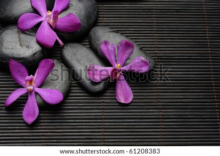 Pink orchid with Stones Against bamboo stick straw mat - stock photo