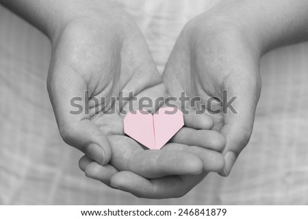 Pink origami heart in human hands. Black and white.