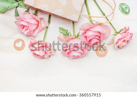 Pink pale roses paper shopping bag and round sign with message for you and heart on white wooden background, top view. Valentine Day or Birthday greeting card. - stock photo