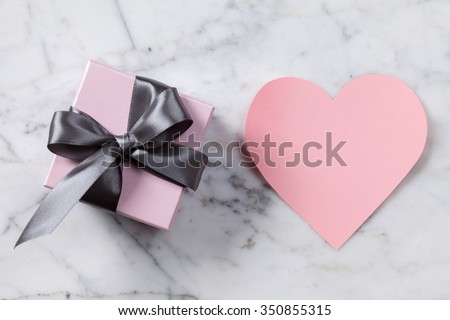 Pink paper heart and gift box on a marble table - stock photo