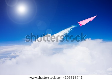 Pink paper plane flying over clouds against blue sky