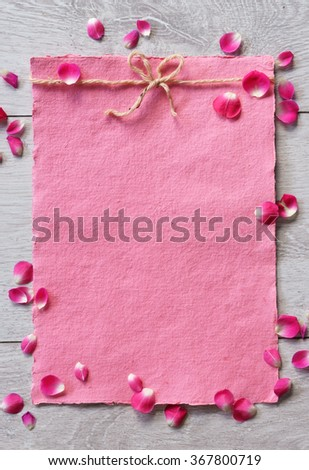 Pink paper with small petals on white wooden background. Valentines Day background and Copy space for your text - stock photo