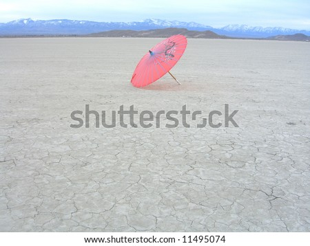 Pink Parasol in the desert - stock photo