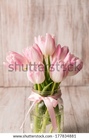Pink pastel Tulips in glass jar vase with pink bow - stock photo