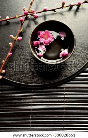 Pink peach blossoms,black small bowl and black tray.Image of Japanese style flower arrangement on spring season - stock photo