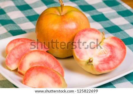 Pink Pearl Apples freshly sliced onto a white plate