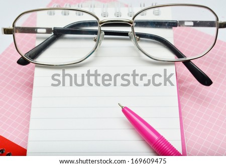 Pink pen notebook and glasses  - stock photo