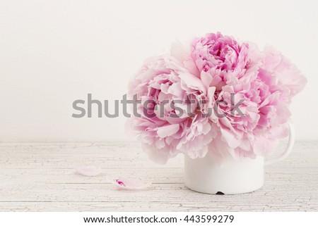 pink peonies in an old enamel mug, copyspace - stock photo