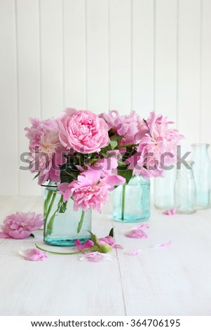 Pink peonies in glass jars on table - stock photo