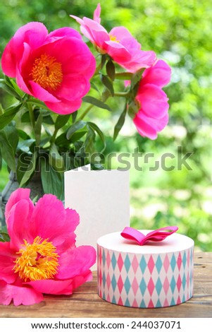Pink peonies in metal vase, gift and empty card for letter