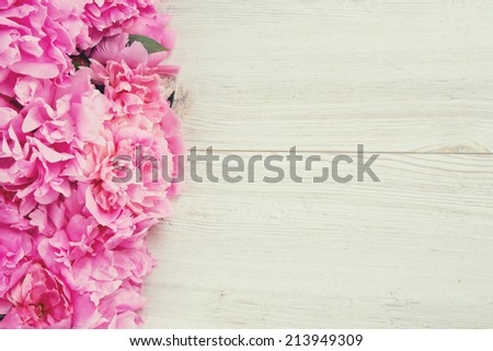 pink peonies on wooden surface - stock photo