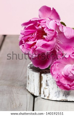 Pink peony flower on wooden table - stock photo