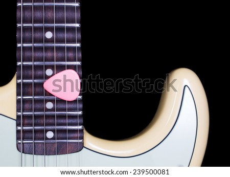 pink pick on scalloped electric guitar rosewood fingerboard close up, isolated on black for music background - stock photo
