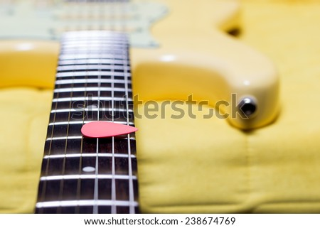 pink pick on yellow electric guitar fingerboard , shallow dept of filed & focus to pick - stock photo