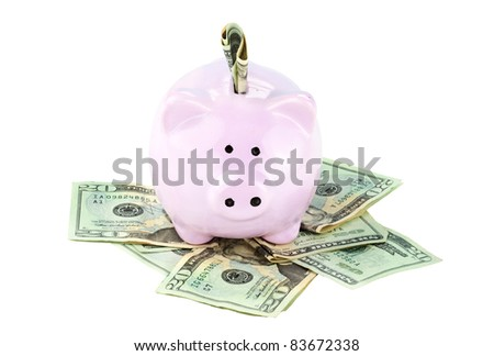 Pink piggy bank and cash isolated on a white background with clipping path included.