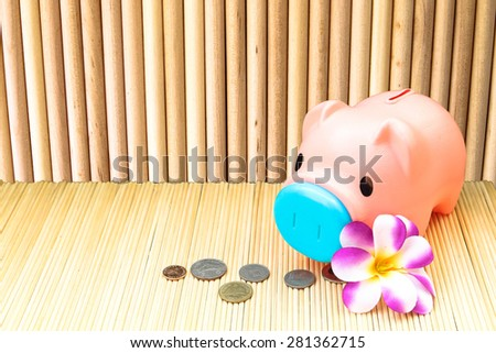 pink piggy bank and coin on round wooden wall background  in vintage tone - stock photo