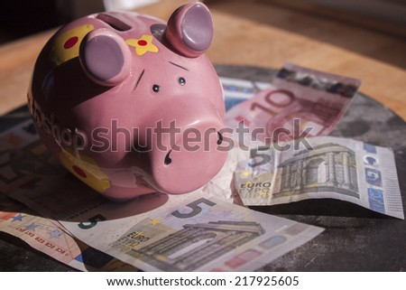 Pink piggy bank and money on a stone plate - stock photo
