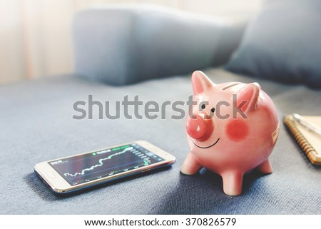 Pink piggy bank and Smart phone with stock market chart place on sofa.money and saving concept.