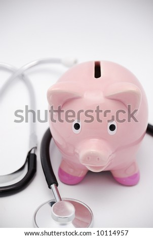 Pink piggy bank and stethoscope - stock photo