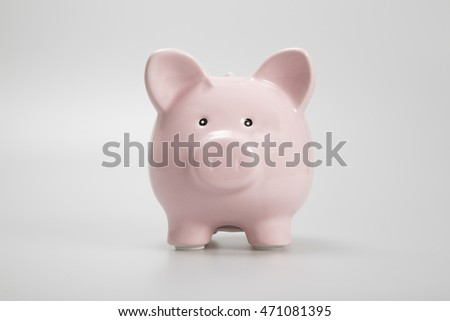 Pink piggy bank facing camera on white background
